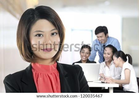 Beautiful Chinese Business woman with colleagues working behind.