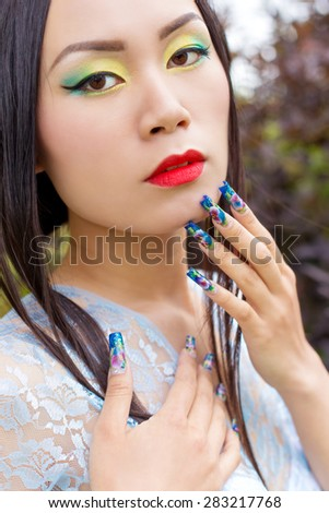beautiful Chinese girl in kimono with long false nails near the face with red lipstick - stock photo