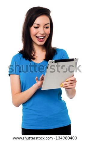 Beautiful chinese girl playing games on tablet device isolated over white.