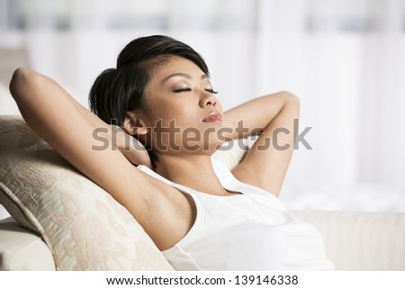 Beautiful Chinese woman sleeping on sofa in the living room  - stock photo