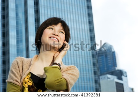 Beautiful chinese woman talks on the phone. Modern building behind her - stock photo