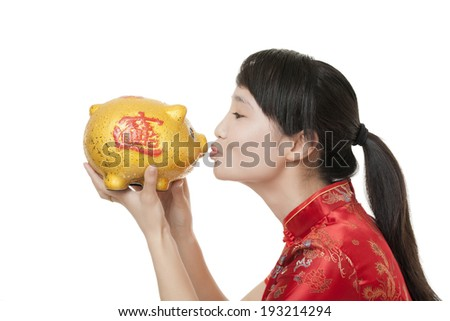 Beautiful Chinese woman wearing a traditional dress known as a Chipao holding a piggy bank isolated on a white background