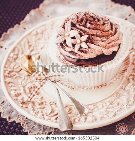 Beautiful chocolate cupcake on vintage plate. Selective focus - stock photo