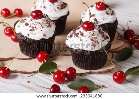 Beautiful chocolate cupcakes with white cream and cherry Black Forest close up on the table. horizontal  - stock photo