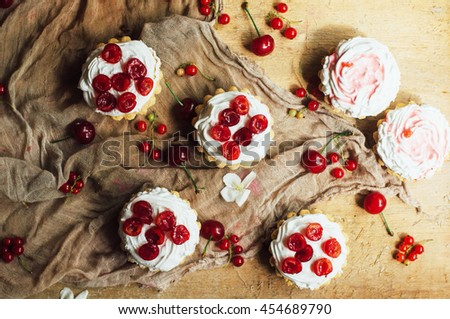 Beautiful chocolate cupcakes with white protein cream and cherry. Vanilla cupcakes with  cream frosting and a cherry on top. Cherry Cupcake Shot on wooden table. Ripe red cherries and currant muffin  - stock photo