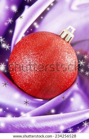 Beautiful Christmas ball on purple satin cloth - stock photo
