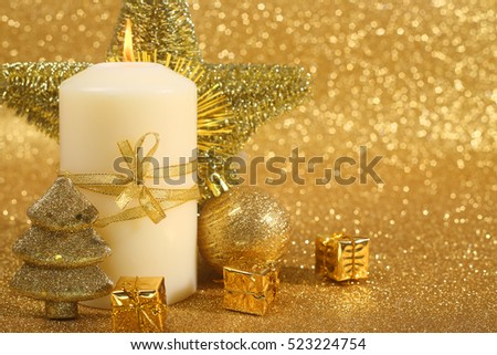 Beautiful christmas candle on golden glitter background with copy space