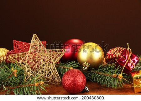 Beautiful Christmas decorations on fir tree on table on brown background