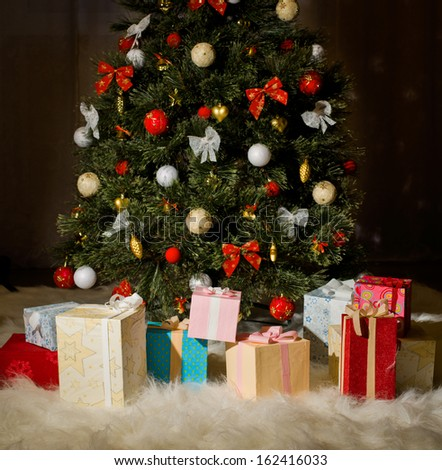 beautiful Christmas firtree with gift on dark brown background