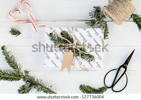 Beautiful Christmas gift with blank tag. Decorated naturally with pine tree twigs and twine over a white background with candy canes. Image shot from above.