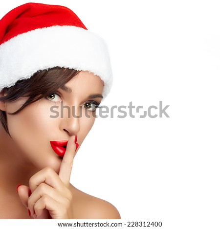 Beautiful Christmas girl in Santa hat doing a hush sign. Red lips and manicure. Closeup portrait isolated on white background with copy space for text - stock photo