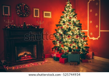 Beautiful Christmas living room with decorated Christmas tree, gifts and fireplace with the glowing lights at night