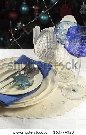 Beautiful Christmas table setting in front of Christmas Tree, with blue theme crystal wine goblet glasses and turkey tureen. - stock photo