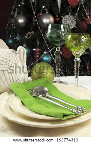 Beautiful Christmas table setting in front of Christmas Tree, with green crystal wine goblet glasses and turkey tureen. - stock photo