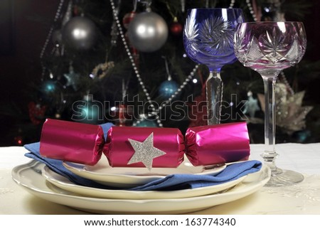 Beautiful Christmas table setting in front of Christmas Tree, with pink and blue long stem crystal wine glasses and decorations - stock photo