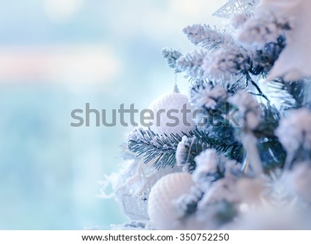 Beautiful Christmas tree border, gentle white bauble hanging on pine twig covered with snow over blue background, stylish winter decoration - stock photo