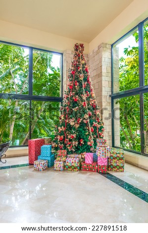 Beautiful christmas tree decorated and lighted with gifts and ornaments for Christmas and for New Year Eve in the lobby, hall of the hotel, office, restaurant. - stock photo