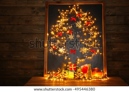 Beautiful Christmas tree drawn on board and decorated with garland, on wooden background