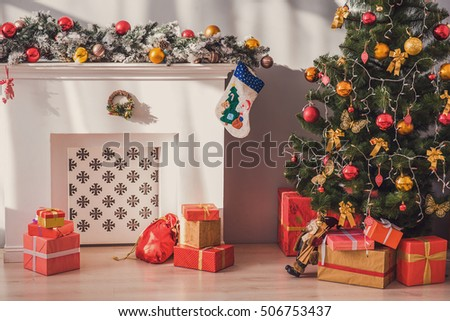 Beautiful Christmas tree, gift boxes and fireplace at home