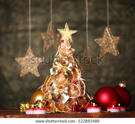 beautiful christmas tree of dry lemons with decor, on grey background - stock photo