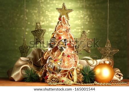 beautiful christmas tree of dry lemons with decor, on shine green background - stock photo