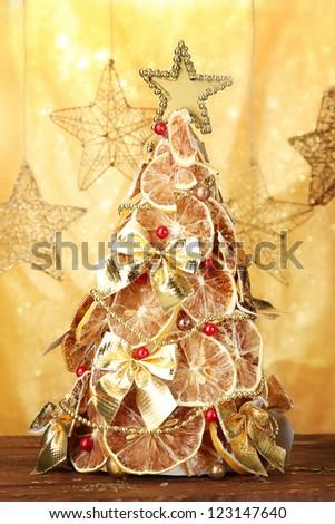 beautiful christmas tree of dry lemons with decor, on yellow background - stock photo