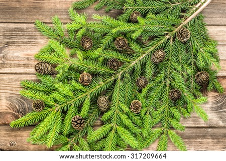 Beautiful christmas tree twigs of spruce with cones arranged on rustic wood background useful as christmas background in vintage style. - stock photo