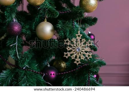 Beautiful Christmas tree with dark purple balls and golden stars - stock photo