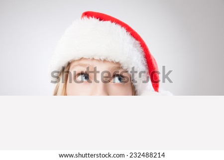 Beautiful christmas woman in santa hat holding empty board and looking to the right isolated on white background - stock photo