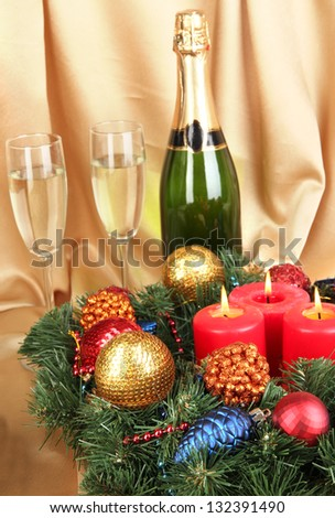 Beautiful Christmas wreath in composition with champagne on gold fabric background - stock photo