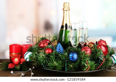 Beautiful Christmas wreath in composition with champagne on room background - stock photo