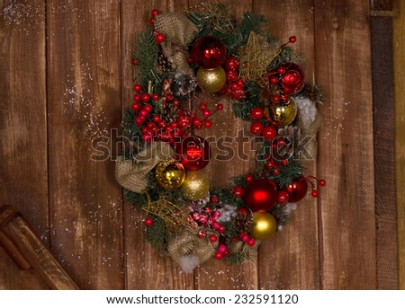 Beautiful Christmas Wreath with Red and Gold Balls and Red Cherries Hanging on the Brown Wooden Wall. - stock photo