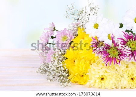 Beautiful chrysanthemum flowers on table on light background