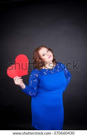 Beautiful chubby girl in blue elegant dress holding a red heart - stock photo