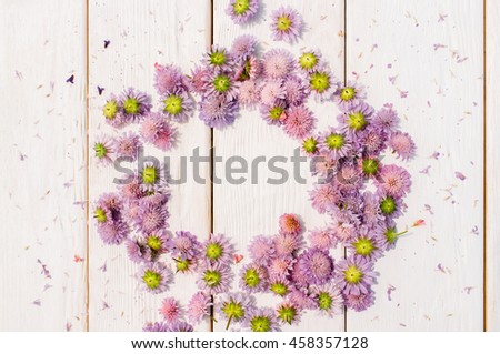 Beautiful circlet of purple aster flowers on white wooden background. Delicate floral composition with free space in center of wreath - stock photo