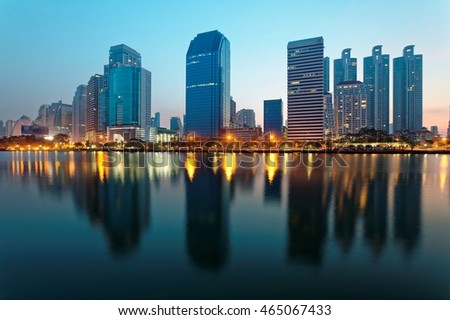 Beautiful city skyline of Bangkok at dawn with lakeside skyscrapers and reflections ~ Morning view of glass curtain walled buildings reflecting on smooth lake water in Benjakiti Park, Bangkok Thailand