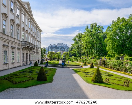 Beautiful cityscape view of famous Mirabell Gardens (public place) with the old historic Fortress Hohensalzburg in background. Green flowerbed with walkways in park under blue sky and clouds.