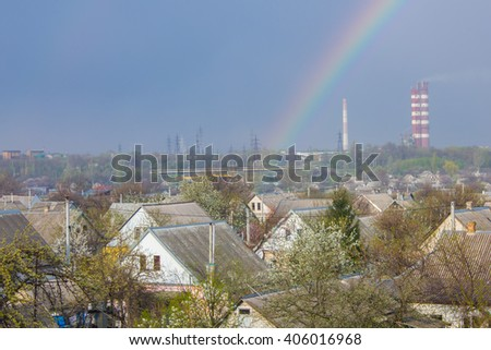 beautiful classic rainbow across in the blue sky after the rain over the suburb and the plant's tower  - stock photo