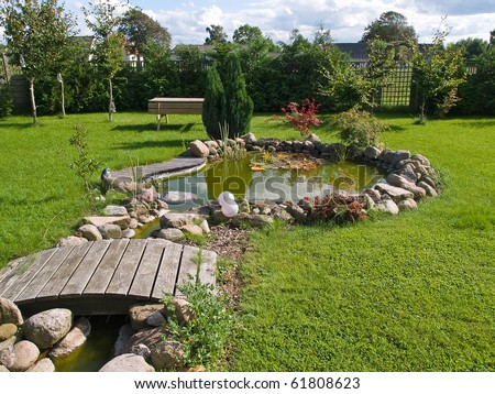 Beautiful classical garden fish pond surrounded by grass gardening background - stock photo