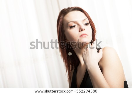 Beautiful classy red hair girl in black dress pondering - stock photo
