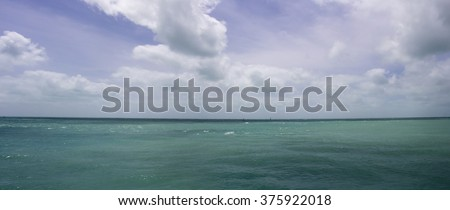 Beautiful clear pristine aquamarine  waters of the Indian Ocean near port of Broome, North Western Australia on a cloudy hot morning in summer wet Season  with cloud shadows passing across is calm. - stock photo
