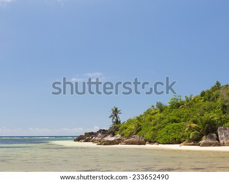 Beautiful clear sea and rocky shore with large stones on the Seychelles, Africa - stock photo