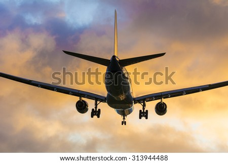 Beautiful close up from a landing airplane during a colorful sky. Typical aviation background. - stock photo