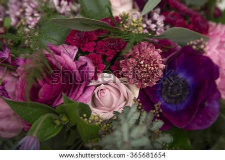 Beautiful close-up of a flower arrangement with purple and pink roses, peonies, anemones and lilac flowers - stock photo