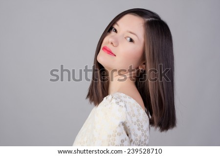 Beautiful close-up portrait of an young woman with short brown haircut wearing red lipstick on studio background. Haircut. Beautiful Girl with Healthy Straight Blond Hair. Hairstyle - stock photo