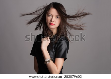 Beautiful close-up portrait of an young woman with short brown haircut wearing red lipstick on studio background. Haircut. Beautiful Girl with Healthy Straight Blond Hair. Hairstyle