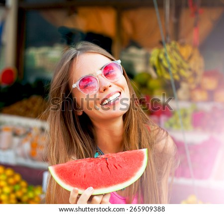 Beautiful close-up portrait of young model girl,with watermelon.Natural make-up.Fashion tropical style.Wear pretty colorful clothes ,and ,bright glasses. Having fun and smiling near fruit market. - stock photo