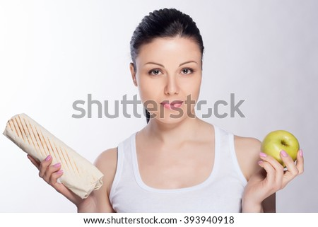 Beautiful close-up portrait of young woman choosing between a green apple, kebab and shaorma. Healthy food concept. Skin care and beauty. Vitamins and minerals.