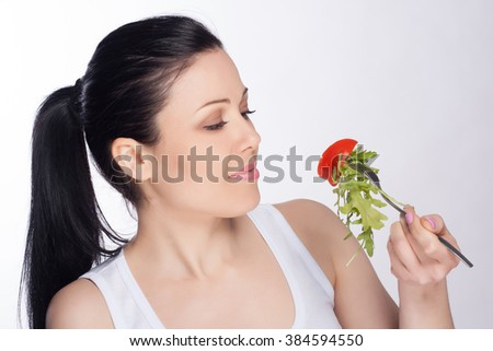 Beautiful close-up portrait of young woman eating salad and vegetables. Healthy food concept. Skin care and beauty. Vitamins and minerals. - stock photo
