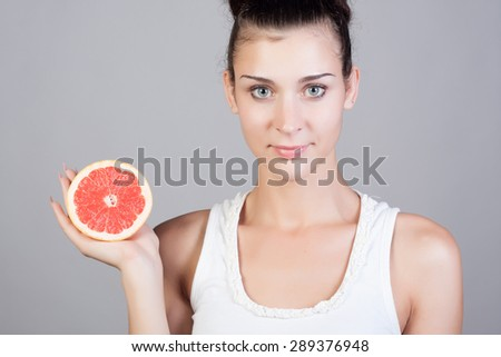 Beautiful close-up portrait of young woman with grapefruit. Healthy food concept. Skin care and beauty. Vitamins and minerals.